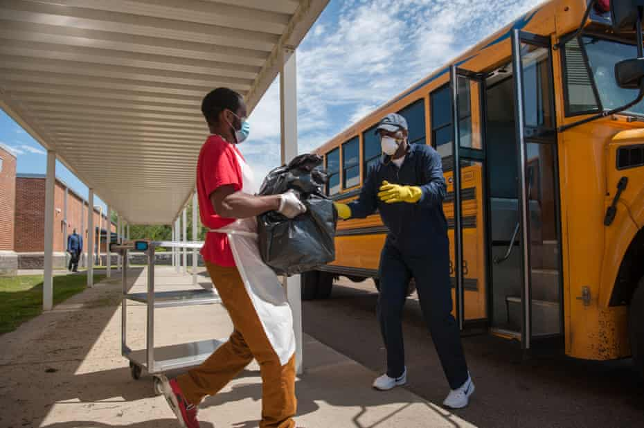 Robert King (right), transportation supervisor for Holmes County Consolidated School District, loads meal deliveries at William Dean Jr. Elementary School in Lexington, Mississippi, on April 1, 2020