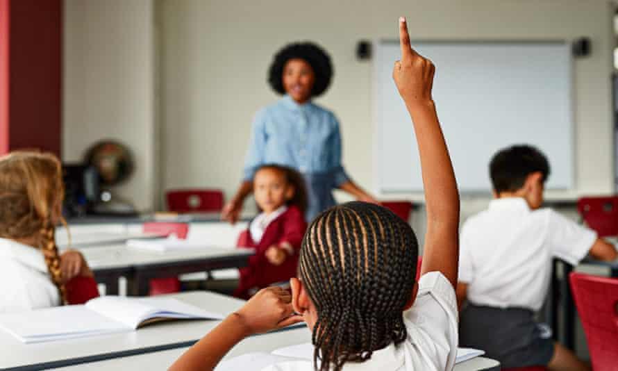 Focus on schoolgirls raised hand in classroom with teacherChildren at modern school facility
