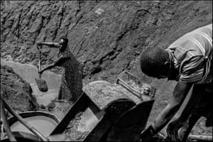 A woman digs alongside a man who is trying to repair a crushing and washing machine at an informal or artisanal mine