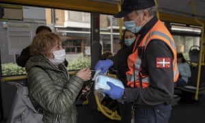 A volunteer hands out masks to bus passengers in San Sebastian.