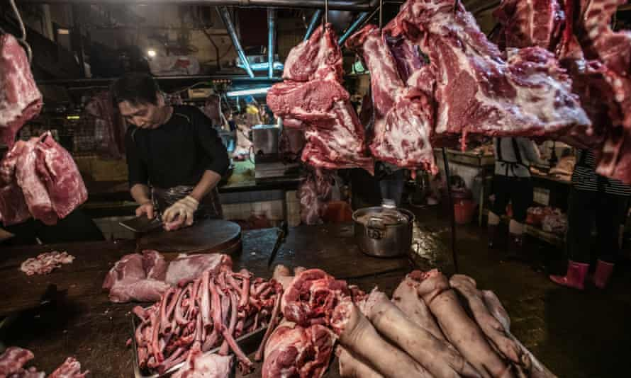 Pig carcasses are chopped and hung for sale display at a Taipei wet market.