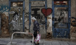 A woman passes an abandoned house in Athens. Alexis Tsipras said his government was 'doing whatever it should in order to reach ... an honest and mutually beneficial agreement' with its creditors.