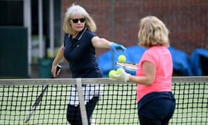 Players at a north London club wear gloves to pick up and serve balls during a socially distanced tennis match.