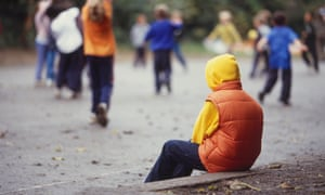 Rear view of a child wearing a hooded top, sitting on his own in a playground.