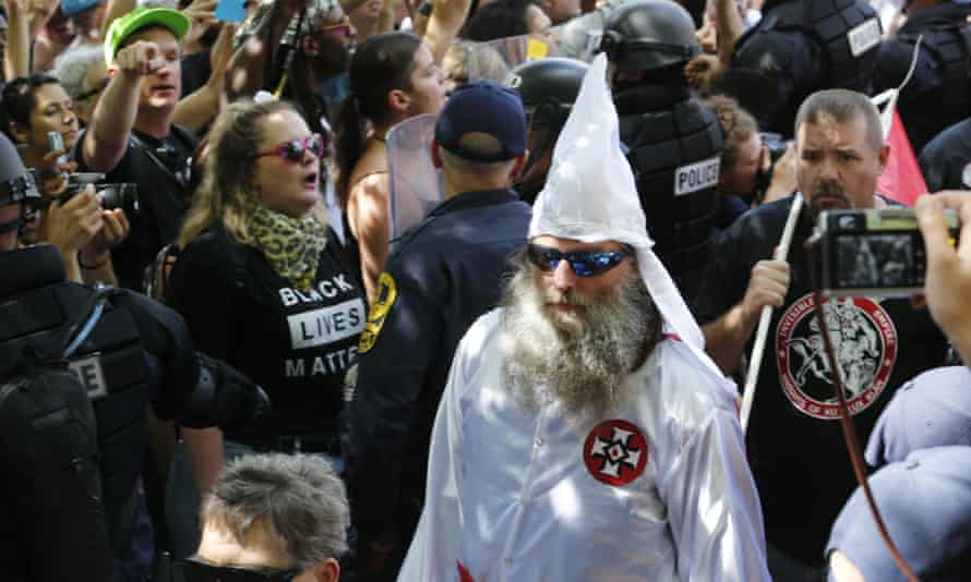 Members of the KKK are escorted by police past a large group of protesters during a KKK rally in Charlottesville, Virginia, in July this year.