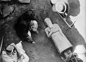 The statue of Ishtup-Ilum emerging from the palace throne room in 1936. A large statue of a man, lying on its back, is excavated by an archaeologist and Syrian workmen.