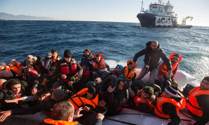 Rescuers help refugees from their inflatable dinghy