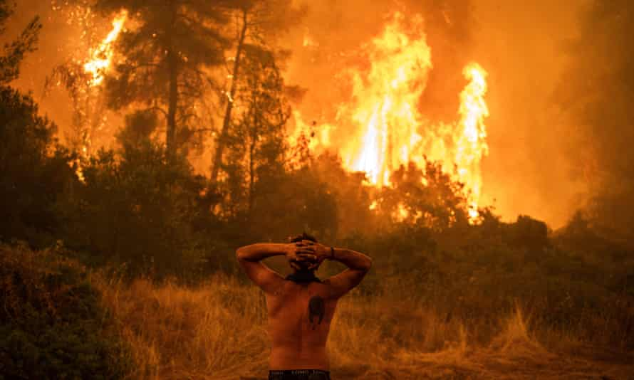 A local resident reacts as he observes a large blaze during an attempt to extinguish forest fires approaching the village of Pefki on Evia island, Greece's second largest island