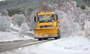 A snowplough works to clear snow from the A938 between Carrbridge and Dulnain Bridge in the Scottish Highlands.