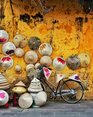 A bicycle is propped in front of a golden-coloured wall which has traditional Vietnamese hats hung on it and around it.