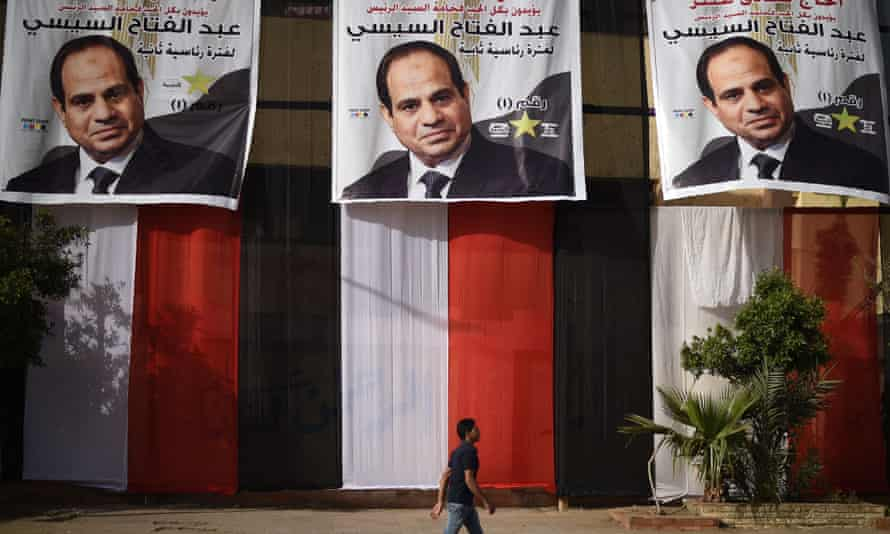 An Egyptian youth walks past a polling station in the capital Cairo's western Giza district on March 25, 2018 ahead of the vote scheduled to begin the following day, decorated on the outside with giant privately-sponsored electoral posters depicting incumbent President Abdel Fattah al-Sisi and giant pieces of cloth stacked together to show the colours of the Egyptian flag. / AFP PHOTO / MOHAMED EL-SHAHEDMOHAMED EL-SHAHED/AFP/Getty Images