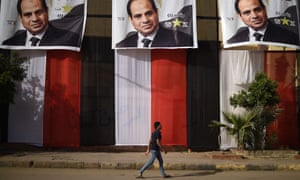 An Egyptian youth walks past a polling station in the capital Cairo's western Giza district on 25 March.