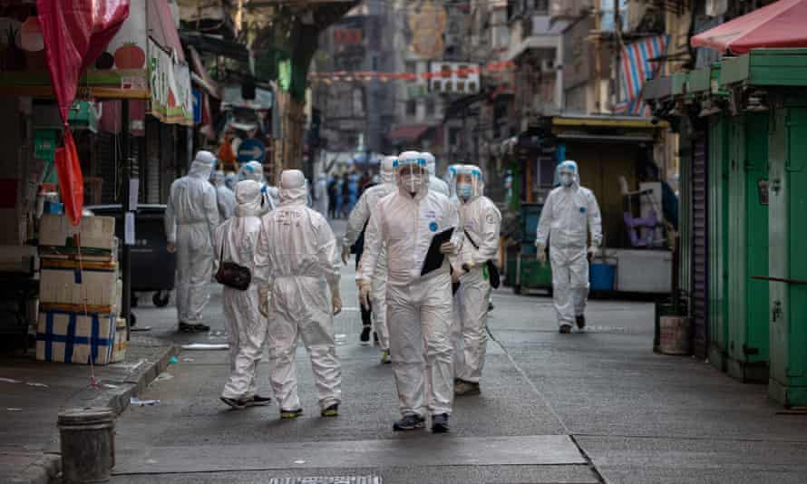 Civil servants in protective face masks and gowns enforce a lockdown in Jordan, Hong Kong