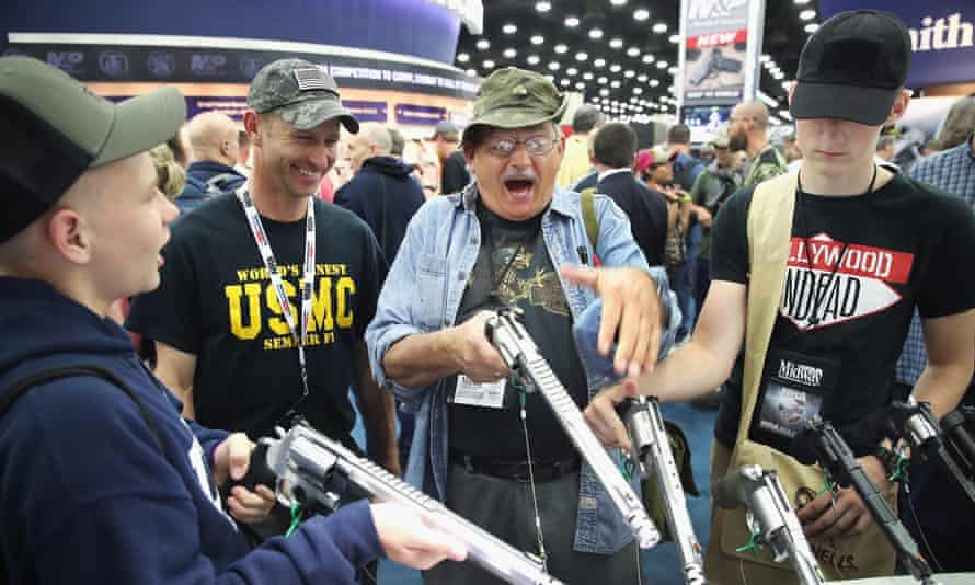 Gun enthusiasts look over Smith & Wesson pistols at the annual NRA event on Saturday in Louisville, Kentucky.