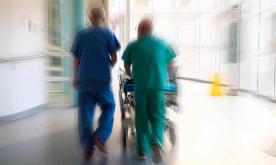 Doctor and a surgeon push a patient on a hospital bed trolley through accident and emergency department of a UK hospital.