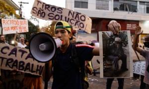 Manifestante mostra uma foto de Ricardo Nascimento, durante as manifestações que se seguiram à morte do catador. Fotografia: NurPhoto via Getty