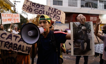 A demonstrator holds a picture of Ricardo Nascimento during protests over the catador's death.