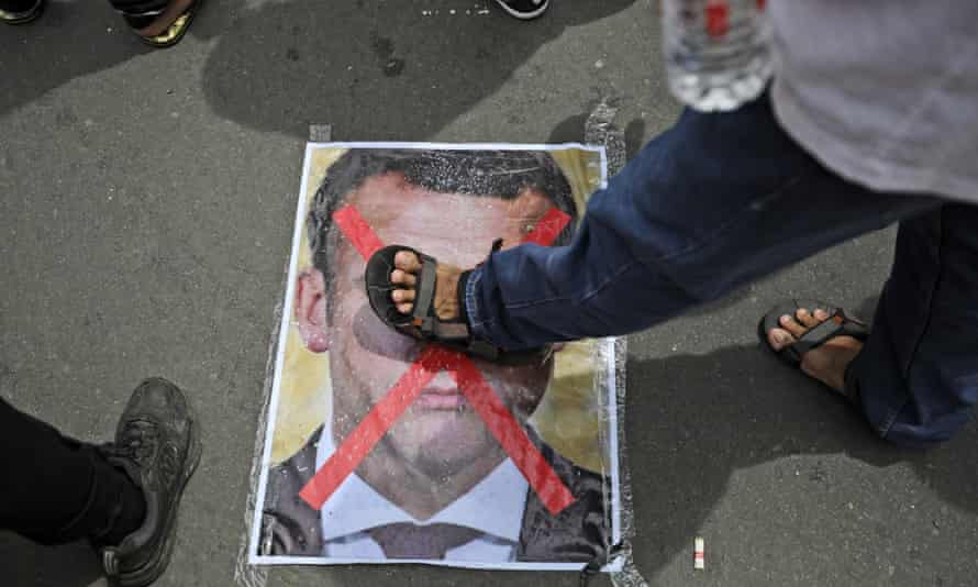 A man steps on a defaced portrait of French president Emmanuel Macron during a protest outside the France Embassy in Jakarta, Indonesia on Monday.