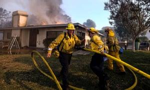 Firefighters work in Bel-Air as wildfires rage.