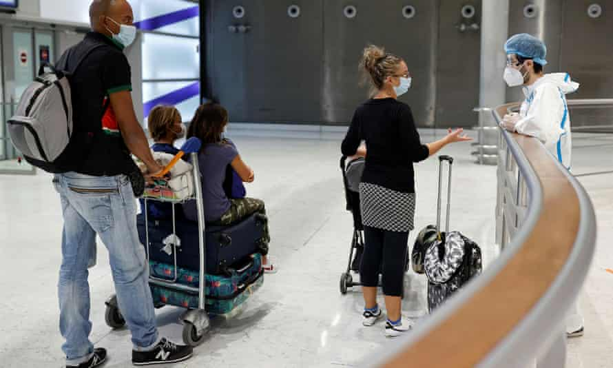 A health worker wearing protective gear talks with passengers on arrival at Charles de Gaulle airport