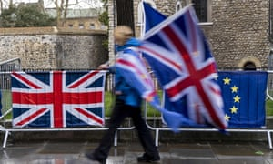 A protester carrying flags walks past the Union (L) and EU flags of anti-Brexit activists near the Houses of Parliament in London on March 18, 2019.