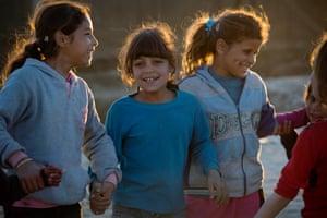 Girls play as the sun sets in the refugee settlement in Zahlé, Lebanon