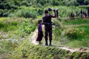 A member of Border Guard Bangladesh stops a Rohingya girl from crossing on to the Bangladesh side, in Cox's Bazar, Bangladesh.