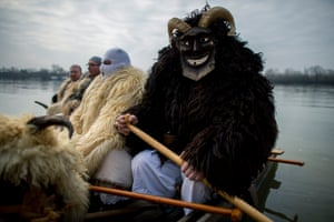 Men wearing costumes with horns and masks prepare to paddle a boat across the River Danube to participate in the traditional carnival.
