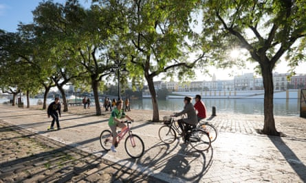 Cyclists riding along the banks of the Guadalquivir river.