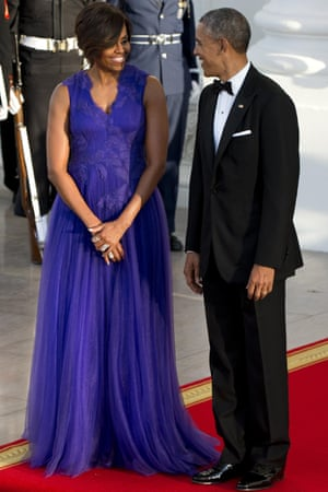 Barack and Michelle Obama wait to greet their guests of honor. The first lady wears a dress by Japanese designer Tadashi Shoji.