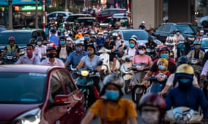 Motorbike riders with protective face masks travel during the afternoon peak hour on 31 July 2020 in Hanoi, Vietnam.