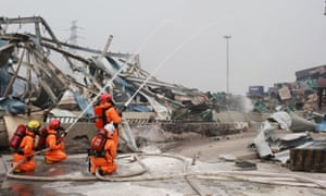 Firefighters wearing chemical protective clothing work at the site of explosion in Tianjin, north China, on Saturday.