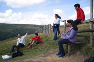 A family pauses for a quick break as they hike through the hills surrounding Dovestone reservoir.
