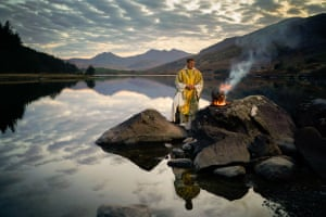 The Reverend Stuart Elliott blesses the new fire as part of his Service of New Light for Easter Eve on the shore of Llynnau Mymbyr in Snowdonia in April 2020.