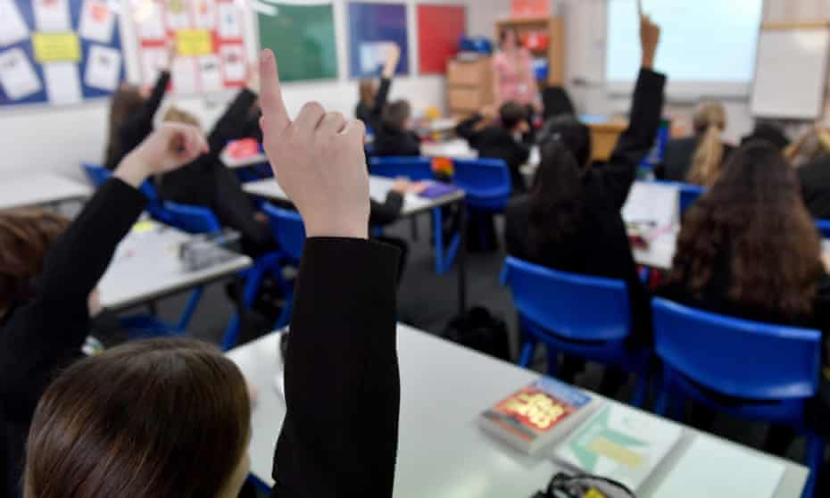 Pupils raise their hands in a lesson as they return to school in Stalybridge, England.