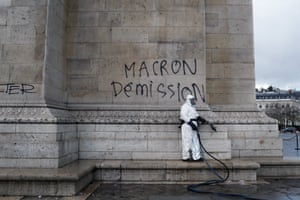 """A worker about to remove graffiti reading """" Macron resignation"""" on the Arc de Triomphe"""