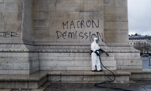 A cleaner is trying to remove a graffiti calling for the resignation of Macron from the Arc de Triomphe.