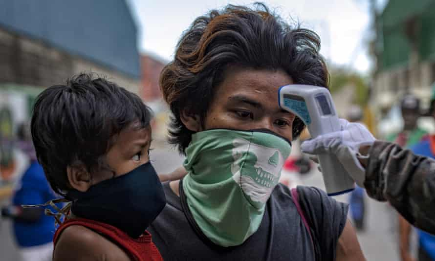 A man and his son have their temperature checked before being allowed to enter a slum area in Manila, Philippines. Civil society groups have warned that the coronavirus pandemic will hit hardest the poorest people in the poorest countries.