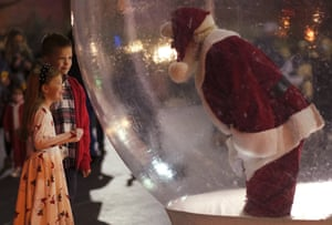 A young girl and boy visit with the Santa in the snow globe during Automobile Alley's Lights on Broadway. The snow globe was used as a way to keep social distancing for COVID-19, but still, let children see Santa. (Doug Hoke/The Oklahoman via AP)