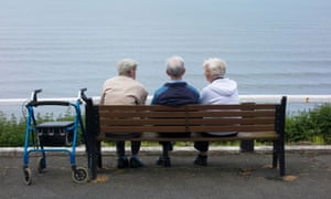 Two elderly men and an elderly woman sitting on bench overlooking sea.