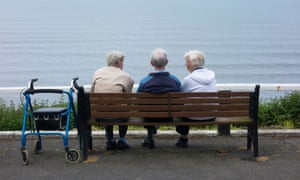 Two elderly men and an elderly woman sitting on bench overlooking sea. Saltburn by the Sea, North Yorkshire