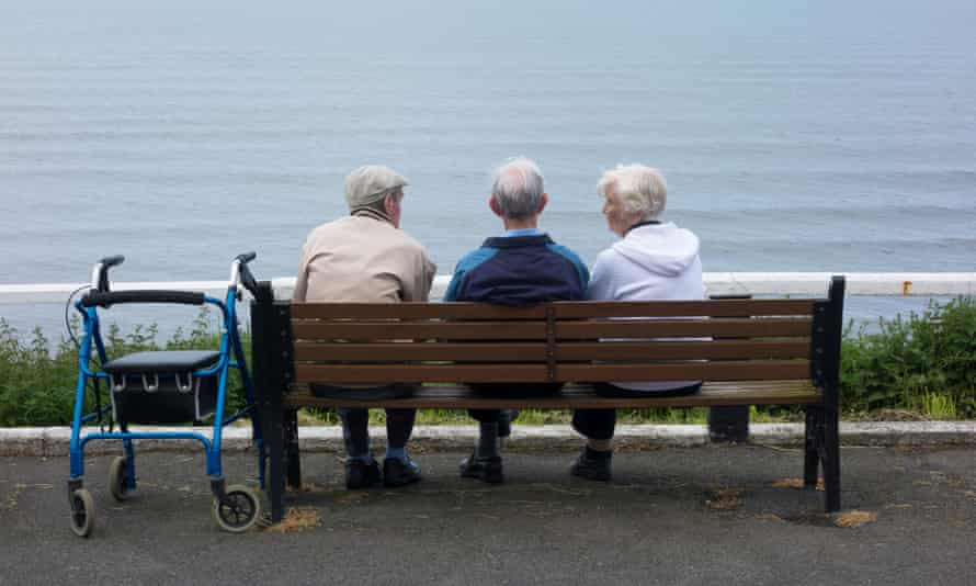 Two elderly men and an elderly woman sitting on bench overlooking the sea.