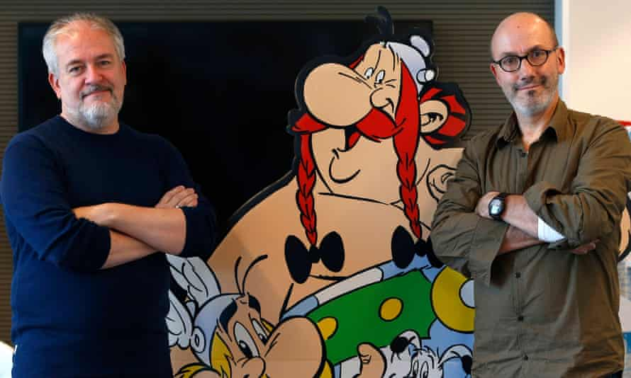 Author Jean-Yves Ferri and illustrator Didier Conrad standing next to a cardboard cut-out of Obelix