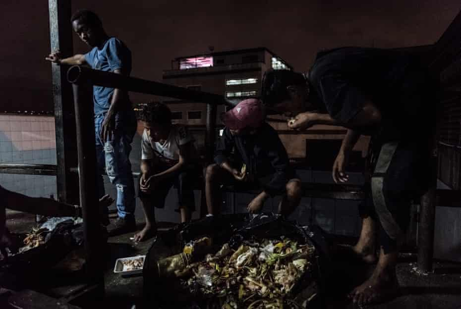 Children look for food in a rubbish dump in an alleyway behind a large shopping centre. According to Cáritas, 53% of families have had to look for food in unconventional places, often meaning among rubbish.