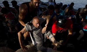 An elderly refugee is being helped to get out of a dinghy after he crossed with others from Turkey to Lesbos island, Greece, on Tuesday.