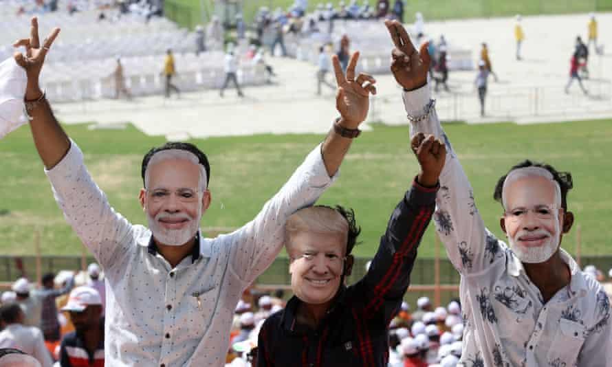 People wear masks of Modi and Donald Trump.