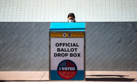 A woman places a ballot in an official ballot drop box in Los Angeles, California.