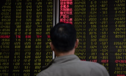 An investor watches stock prices in Beijing on Monday. The main Shanghai index was down more than 6% at one point.