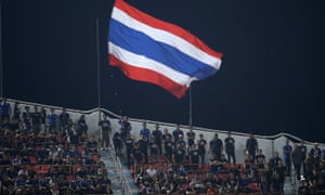 A Thailand flag flies above supporters