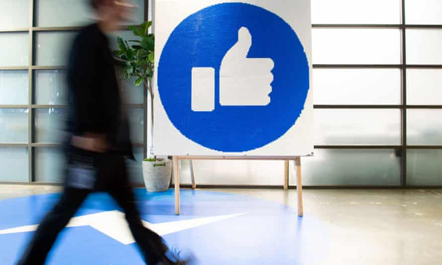 Facebook's headquarters in Menlo Park, California - person walks by large thumbs-up sign